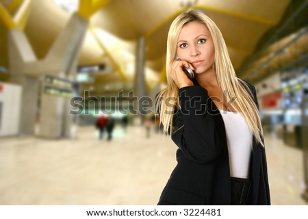 Young caucasian businesswoman communicating on her mobile phone in departure hall while waiting for her flight  for  business travel.