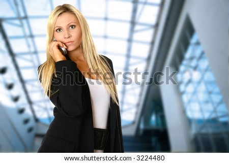 Young caucasian businesswoman talking on the phone, against interior corporate building.
