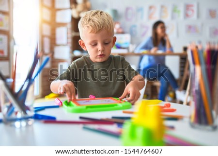 Young caucasian child playing at playschool with teacher. Mother and son at playroom drawing a draw with color pencils, young woman at the background sitting on desk.