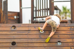 Young caucasian child playing on the playground, climbing on the wooden wall