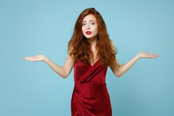Young caucasian confused mistaken redhead angry expressive irritated curly woman 20s in red party evening dress gown spreading hands oops gesture isolated on pastel blue background studio portrait