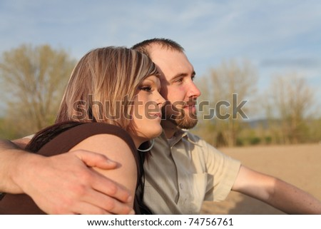 young Caucasian couple close-up sitting on beach outdoors