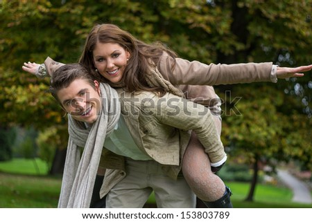 Young caucasian couple in love piggybacking at a park in austria in autumn