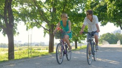 Young Caucasian couple smiles while riding bicycles down a scenic green avenue. Beautiful blonde girl and her handsome boyfriend riding their bikes along a picturesque sunlit park in the summertime.