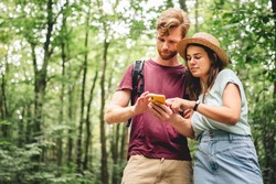 Young caucasian couple uses a smartphone to navigate in the forest. Hiking tourists orientation on the terrain using an online map, an application in a smartphone. GPS for building a route for a walk.