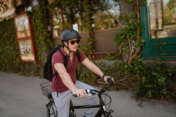 Young caucasian cyclist with helmet and sunglasses on a bicycle in front of the window