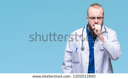 Young caucasian doctor man wearing medical white coat over isolated background feeling unwell and coughing as symptom for cold or bronchitis. Healthcare concept.