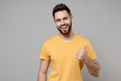 Young caucasian european happy bearded satisfied attractive man 20s wearing casual yellow basic t-shirt show thumb up like gesture isolated on grey background studio portrait People lifestyle concept
