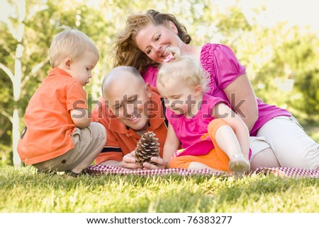 Young Caucasian Family Enjoying Pine Cones at The Park Together.