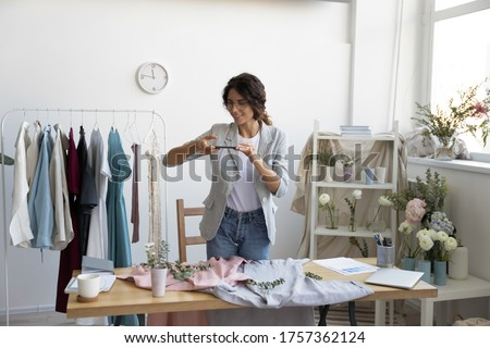 Young Caucasian female blogger or influencer photograph clothes on smartphone at home, millennial woman shoot clothing shopping haul on cell, modern fashion designer picture new dresses on camera