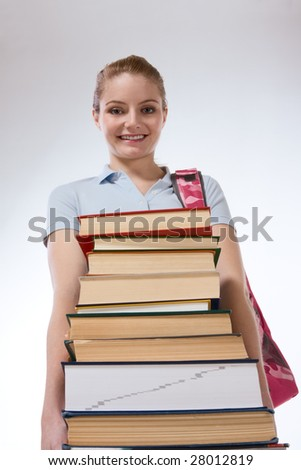Young Caucasian female college student with backpack holding huge pile of educational books from library (low angle view)