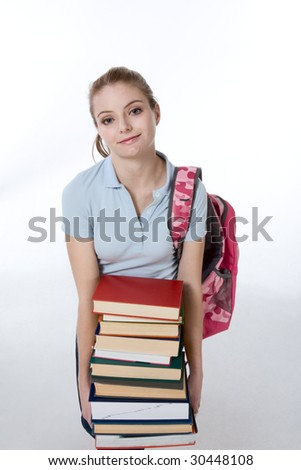 Young Caucasian female college student with backpack holding huge pile of educational books from library (high angle view)