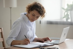 Young Caucasian female doctor in white medical uniform sit at desk in hospital work on laptop make note in register. Woman nurse or GP fill patient anamnesis in journal, use computer