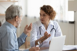 Young Caucasian female doctor in white uniform consult senior male patient at meeting in private clinic. Caring woman GP talk speak with mature man at consultation in hospital. Geriatrics concept.