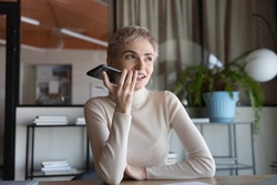 Young Caucasian female employee sit at workplace talk speak on speakerphone on cellphone. 30s businesswoman record audio message or smartphone, use virtual digital voice assistant on modern gadget.