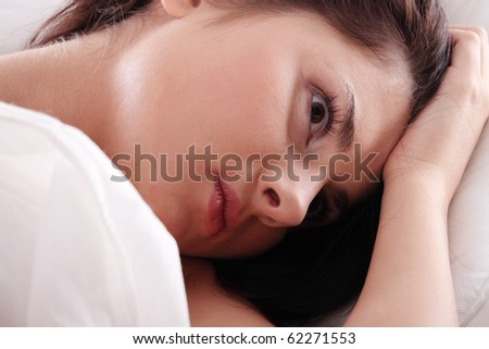 Young caucasian female on bed. Insomnia or depression concept