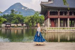 Young caucasian female tourist in hanbok national korean dress at Korean palace. Travel to Korea concept. National Korean clothing. Entertainment for tourists - trying on national Korean clothing