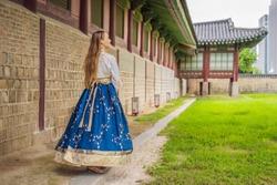 Young caucasian female tourist in hanbok national korean dress. Travel to Korea concept. National Korean clothing. Entertainment for tourists - trying on national Korean clothing