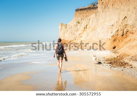 young caucasian female with backpack and  siberian husky dog on beach, hiker woman with dog on seaside