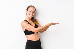 Young caucasian fitness woman posing in a white background holding a copy space on a palm.