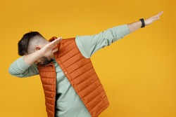 Young caucasian fun man 20s wearing orange vest mint sweatshirt glasses doing dab hip hop dance hands move gesture youth sign hiding covering face isolated on yellow color background studio portrait.