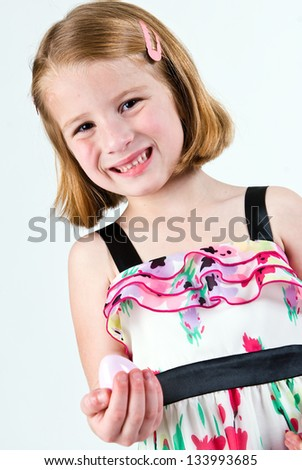 Young Caucasian girl grimacing with plastic Easter egg