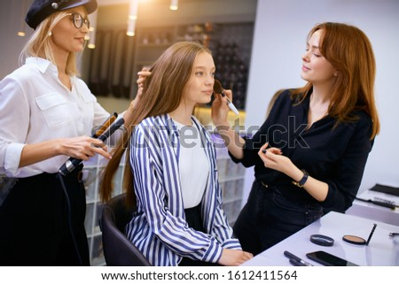 young caucasian girl have full preparation to celebration of birthday or high school graduation, professional confident stylists making hairdo and make-up