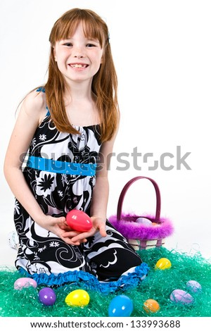 Young Caucasian girl sitting in grass with an Easter egg