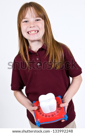 Young Caucasian girl waiting on the tooth fairy holding a large tooth shaped piggy bank with slots to hold baby teeth.