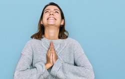 Young caucasian girl wearing casual clothes begging and praying with hands together with hope expression on face very emotional and worried. begging.