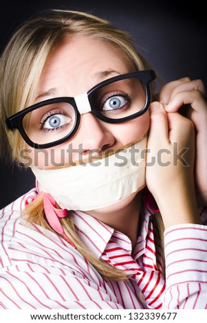 Young caucasian girl wearing nerdy eyeware with frightened expression attempting to remove tape across mouth in a freedom of information concept