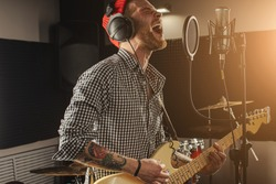 young caucasian gorgeous musician play electric guitar and sing on microphone in recording studio. rockstar perform music. man preparing, practicing before concert.