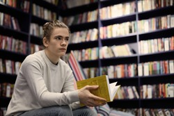 Young Caucasian guy wearing gray sweater spending day at bookstore searching for book on art, holding yellow one in his hands, having uncertain look. People, reading, leisure and knowledge concept