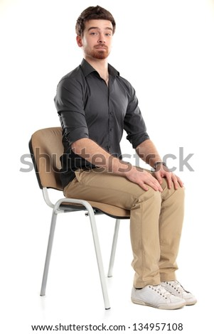 Young caucasian handsome man sitting on the chair isolated over white