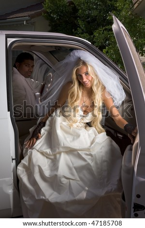 Caucasian happy woman in white gorgeous wedding gown sitting in car