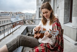Young caucasian hipster/hippie woman in casual clothes playing on Hawaiian guitar, sings a song on a ukulele during self-isolation in the house on terrace. Hobby. Daily life in your own home.