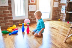 Young caucasian kid playing bowling at kindergarten. Preschooler boy happy at playroom with toys