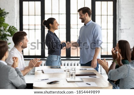 Young caucasian male ceo handshaking with indian female team member on briefing showing respect to her qualification, gratitude for help, recognition of her efforts in developing corporate business