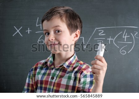 Young caucasian male child is a maths genius with chalk in his hand in front of blackboard with mathematical problem