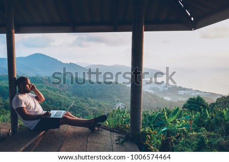 Young caucasian male freelancer talking on mobile phone while working on laptop computer remote. Hipster gut traveler working distantly while enjoying amazon nature landscape during summer vacations