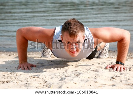 Young caucasian male in sportswear doing push ups at the beach