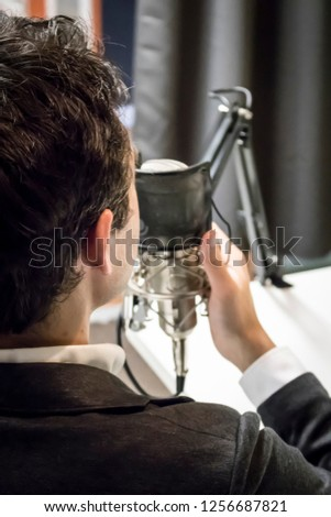 Young Caucasian Male with Dark Hair Speaks into a Microphone in a Podcast Studio #1256687821