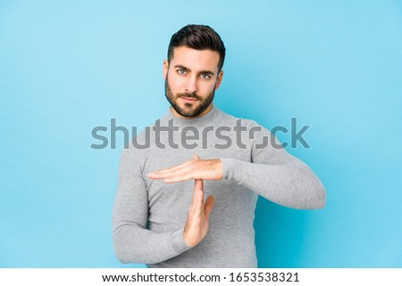 Young caucasian man against a blue background isolated showing a timeout gesture. Stock photo ©