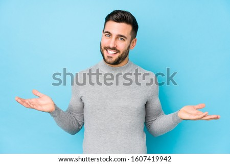 Young caucasian man against a blue background isolated showing a welcome expression.