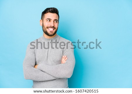 Young caucasian man against a blue background isolated smiling confident with crossed arms.