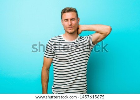 Young caucasian man against a blue wall suffering neck pain due to sedentary lifestyle.