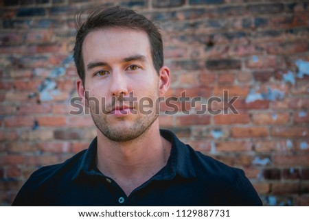 Young caucasian man against a brick background with a concerned facial expression. #1129887731