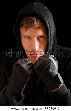 Young caucasian man boxing;  defense position; isolated on black background