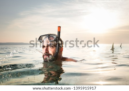 Young caucasian man chased by a shark, predator attack escape in the sea water, swimmer running away from danger, humorous summer holiday concept, copy space