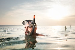 Young caucasian man chased by shark,predator attack escape in sea water,swimmer running away from danger,humorous summer holiday concept,copy space,cancelled vacation due to Coronavirus COVID-19
